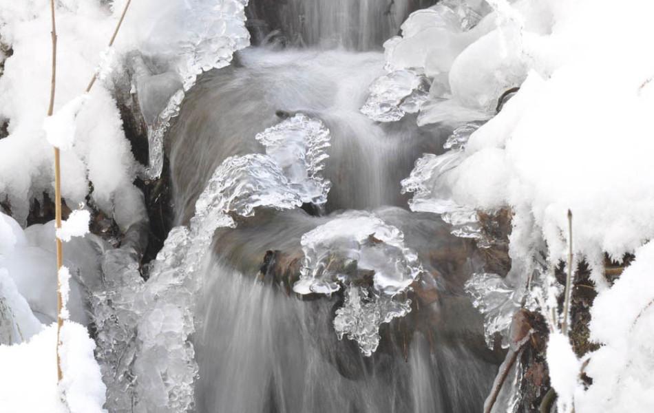 Gefrorener Wasserfall eines kleinen Wiesenbaches